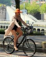 Nortern Spain street fashion with trendy lady on bicycle in Bilbao