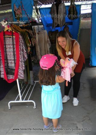 A Manita sales lady not Carolina Hernandez with child customer with a doll needing made to measure