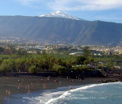 A snow-capped Teide with people in the ocean who swim on Playa Jardin Puerto de la Cruz