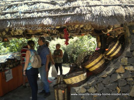 Basketry by stall in thatched ethnographic hut.