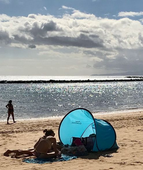 A small, blue beach tent with a mother and a toddler in the warm afternoon sun of November 2018