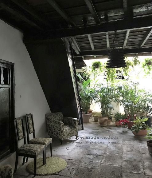 Casa de la Parroquia San Juan Bautista entrance hall, as it leads to a patio with palms