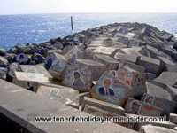 Celebrity images on breakwater stones of Tenerife concert hall Auditorio