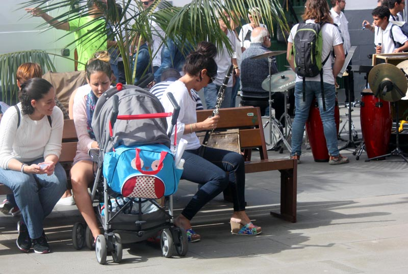 Clarinete player beside mother with pram