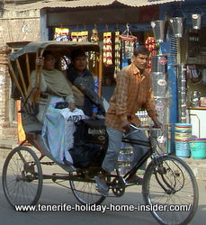 Covered Rickshaw drawn by a cyclist