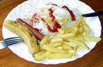 Cuban food of Caribbean rice with a fried egg, a Vienna sausage, fried green Banana and freshly made French fries.