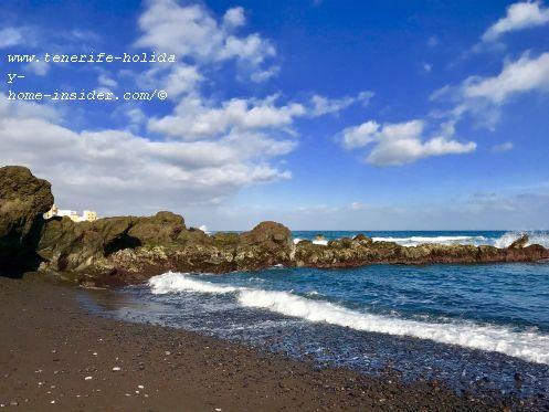 El Charcón beach bay at Playa Jardin embraced by black volcanic rocks