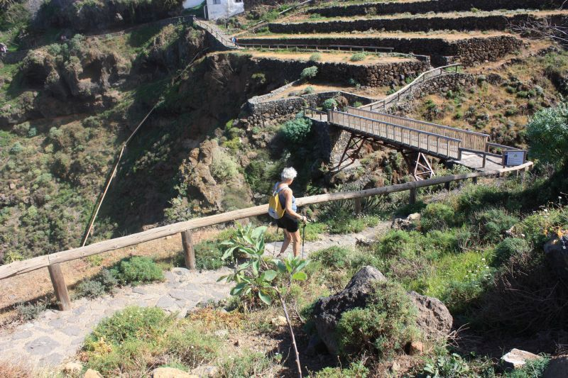 Elderly hiker lady returning from Mirador San Pedro to cross Gordejuela bridge.