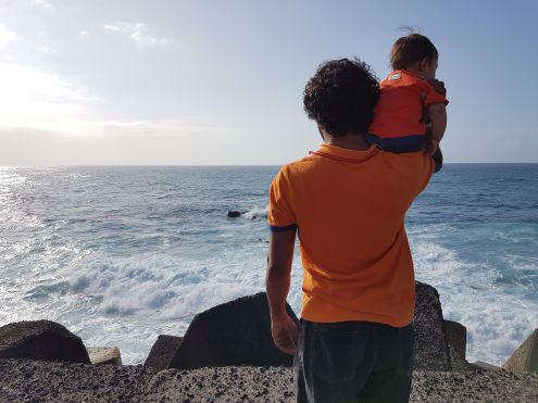 Father with child at the Atlantic by Puerto's dangerous breakwater dubbed Muelle by the locals.