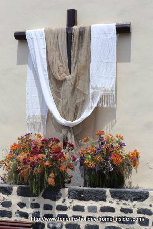 Fiesta de la Cruz a yearly event at the beginning of May with the decorated cross of Puerto de la Cruz portrayed beside.