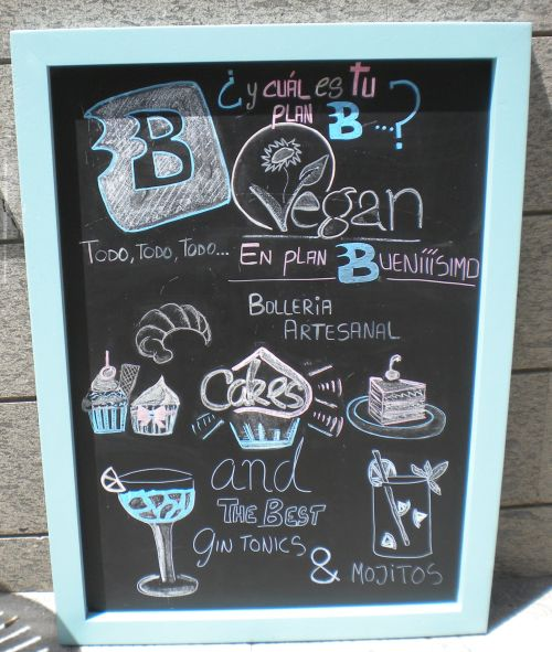 Gay Vegan board with advertisement for food and drinks of the day.
