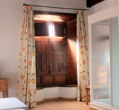 Hotel Rural Bentor with two styles with antique bay window with benches and modern  shower cubicle.