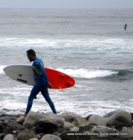 Man with surfboard on El Socorro beach