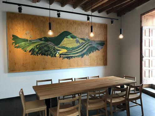 A modern wall hanging with a large wooden table with chairs in a small side room for group events that you see from the patio at Starbucks Tenerife North.