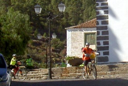 Mountain cyclists appear from Teide by church Santiago Apostol to proceed to Arona.