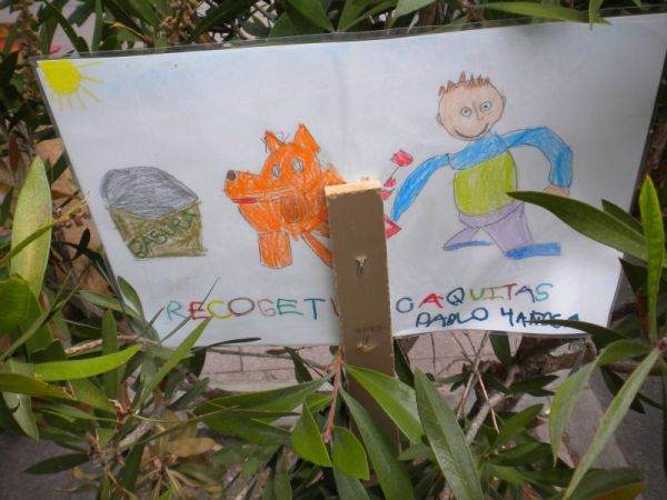 No to dog excrements, says a drawing by a 5 year old to educate adults to pick up their dog litter in the street La Longuera in June 2016. All the road's bushes and trees have such billboards now.