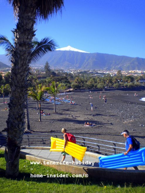 One of unusual pictures with snow on Mount Teide with beachgoers on the way home for lunch.