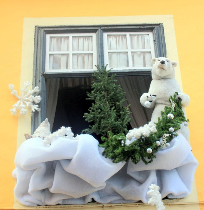 Outside Christmas decoration of ice bear in a window with green pine tree beside.