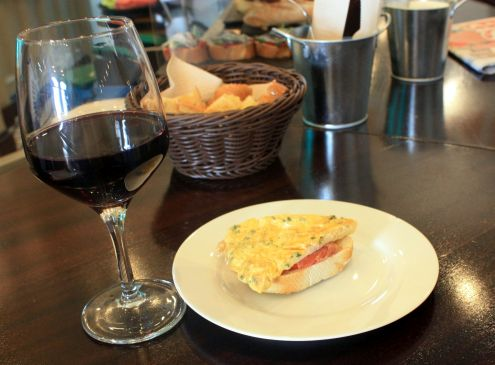 Pintxo with slice of Tortilla on serrano ham above crunchy bread.