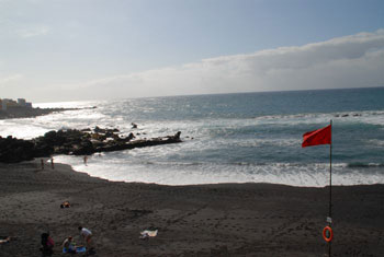 Red beach flag on black Tenerife beach.