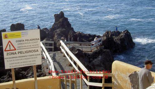 Rogue wave warning danger sign on Punta Brava idyllic spot for fishing