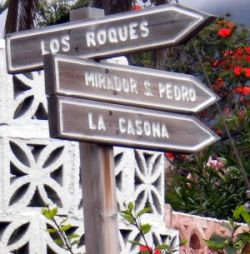 Signpost by Romantica 2 for three ways on Calle Las Rosas straight opposite Calle Los Geranios.