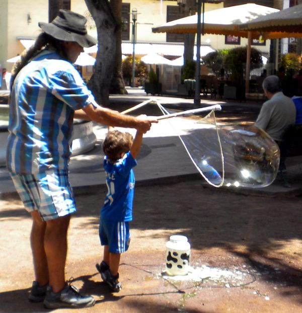 Soap bubbles amusement by father and sun on Plaza Charco.