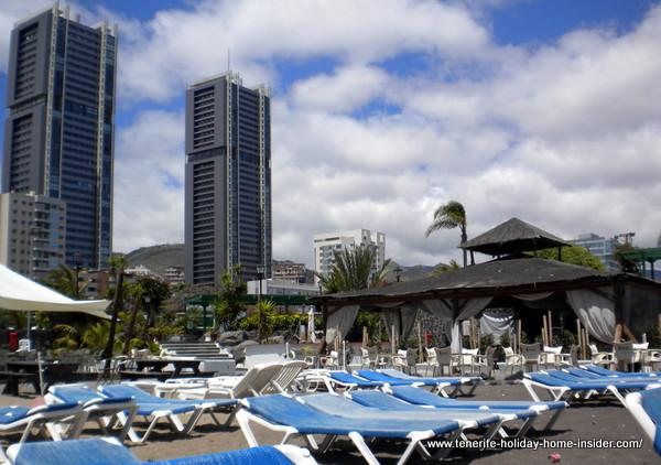 Tallest Tenerife twin towers behind beach restaurant