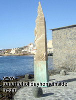 Tenerife sculpture an obelisk yellow like pumice on Playa Grande El Medano