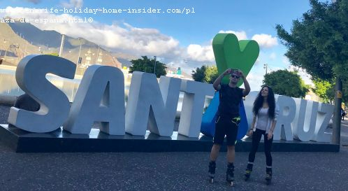 The tourism emblem Santa Cruz with large alphabetic letters and a green heart above its center stands in front of its artificial lake on Plaza España.