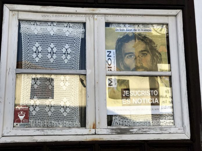 Very artistic casa de la Parroquia window display with Calado curtain on one side and a religious theme on the other