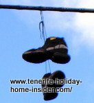 Walking boots suspended from an electrical cable