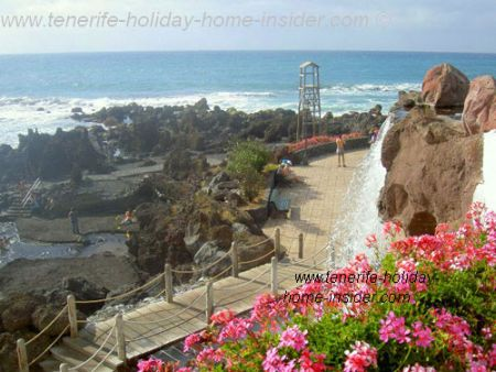 Waterfall landscaping on Tenerife beach with river, bridge and volcanic rocks