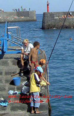 fisher boy, mother and brothers at Puerto Cruz harbor