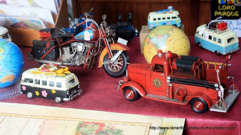 Maps and Metal toys for sale of different sizes as souvenirs or gifts near Plaza del Charco