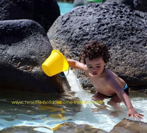 Toddler at the Lago Martianez playing with a bucket in the water.