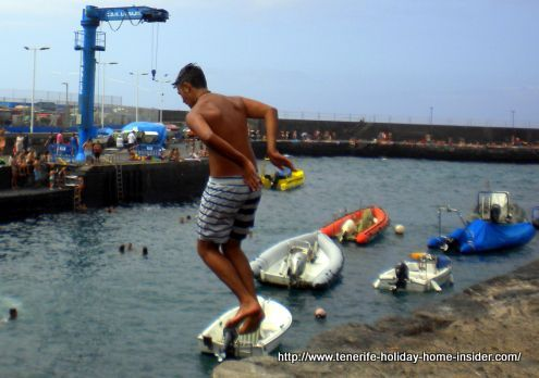 Youngster dives into Puerto Cruz harbor from Muelle platform.